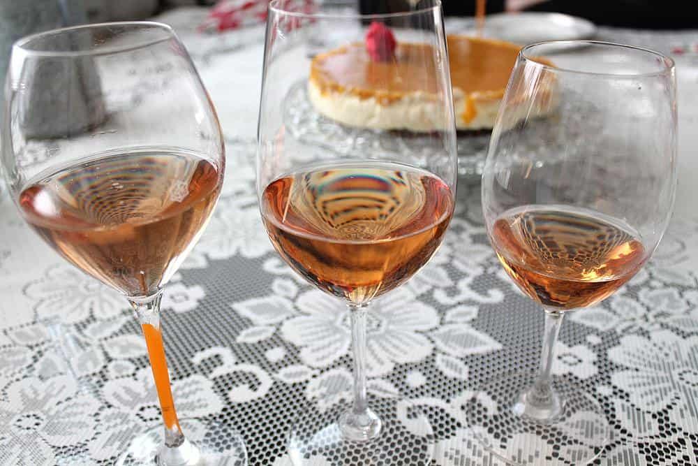 Kolme persikkaista lohenpunaista rosée -viiniä laseissa. Äitienpäivämenu. Viinihetki.